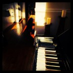 "Image description: A ""selfie"" (self portrait) of my shadow silhouette sitting down during an improv session with my Steinway upright piano in the Front room of my home, looking out through the kitchen and dining area. The photo was captured at sunset."
